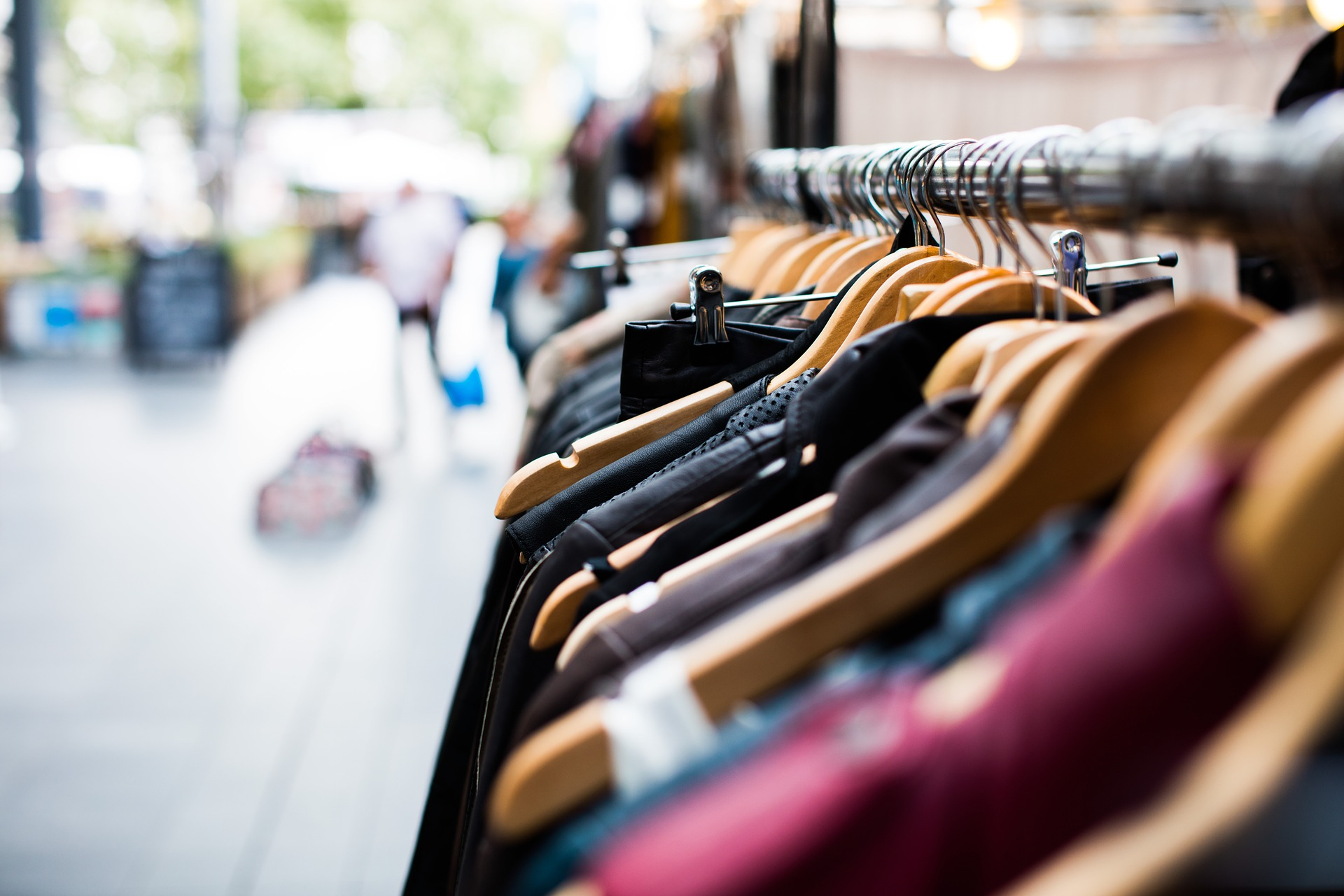 Row of a variety of clothes on a hanger outside.