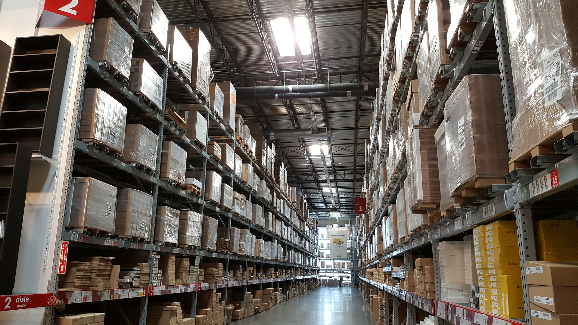 A warehouse with shelves filled with boxes floor to ceiling.